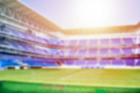 Blurred background of football stadium on beautiful green field with light of sun