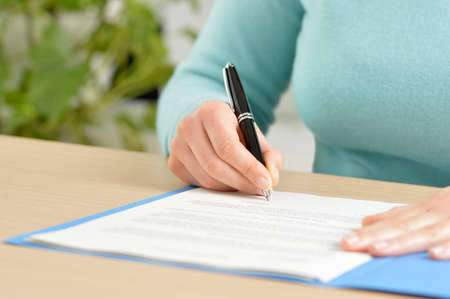 Close up front view portrait of a hand signing a contract on a desktop at office