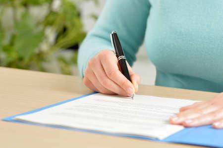 Nahaufnahme der Vorderansicht einer Hand, die einen Vertrag auf einem Desktop im Büro unterschreibt