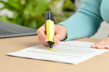 Close up of woman hand underlining a document at home