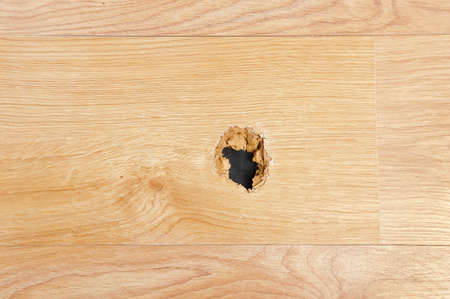 A wooden sheet floor destroyed with a hole at home