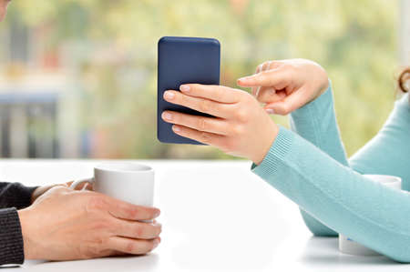 Close up of couple hands using a smartphone and showing
