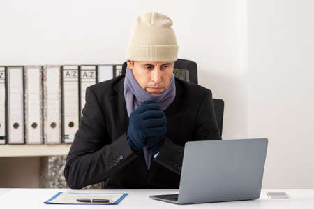 Portrait shot of a cold executive working with a heater failure in winter at office