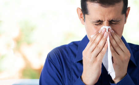 Shot of an young man feeling ill and blowing his nose with a tissue at home and copy space