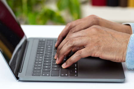 Closeup shot of an unrecognizable man working on a laptop at home