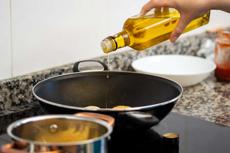 Cropped shot of a woman pouring cooking oil from bottle into frying pan on stove