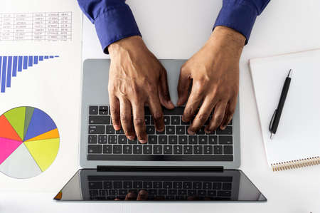 High angle shot of an unrecognizable businessman working on a laptop in an office
