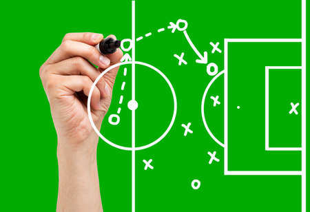 Coach drawing football or soccer game playbook, strategy and tactics with white marker on green background. Reklamní fotografie