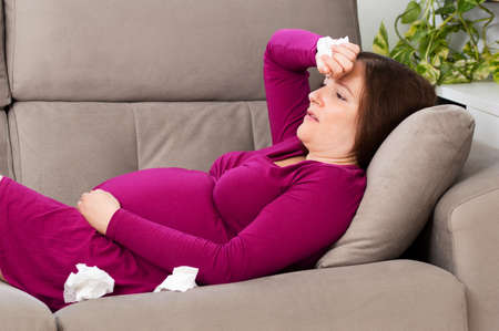 Pregnant woman with hand on forehead suffering headache sitting on a couch in the living room at home