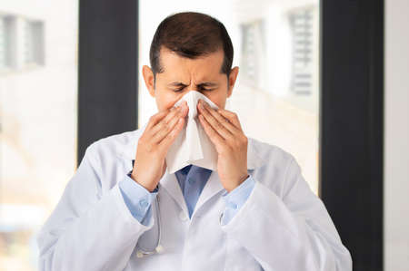 Shot of a male doctor blowing his nose in an hospital Reklamní fotografie