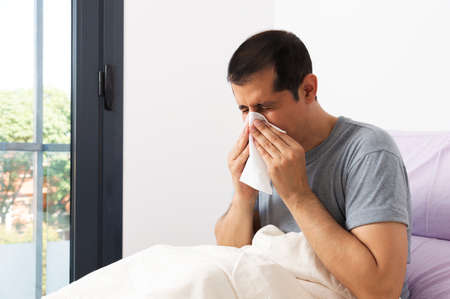 Shot of a handsome young man suffering with the flu while sitting on his bed at home