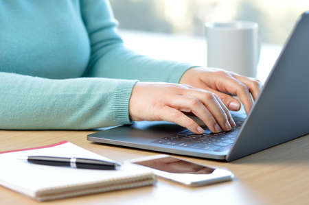 Cropped shot of a woman hands writing on a laptop at home