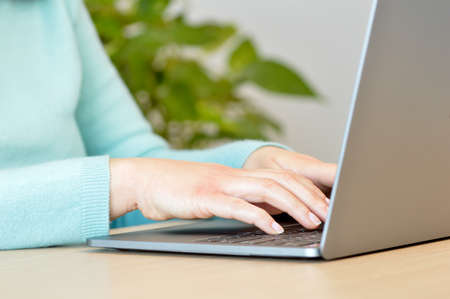 Close up of a woman hands typing on a laptop keyboard with a window and a warm light in the background