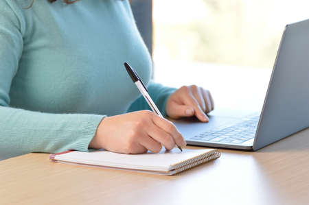 Woman hands taking notes in a notebook with laptop at office