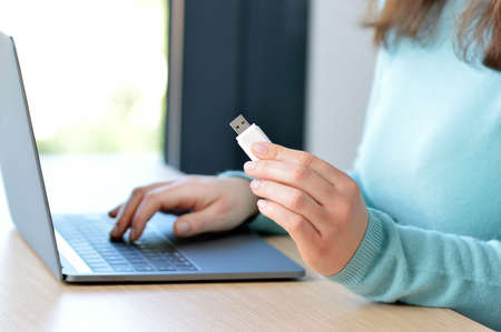 Close up of woman hands on a laptop with a pen drive at home