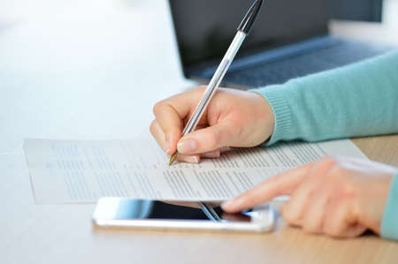 Close up of a woman hand writing or signing in a document on consulting a mobile phone on a desk at home or office Reklamní fotografie
