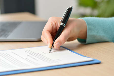 Cropped shot of a businesswoman hand signing a contract on a desk at office