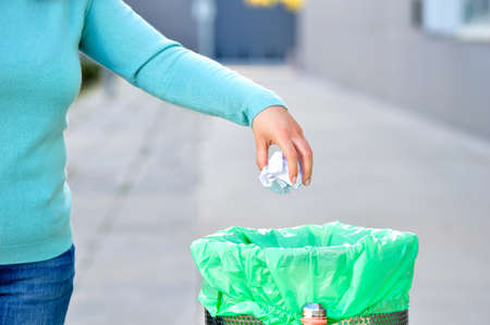 Civic woman throwing garbage in a trash bin a city