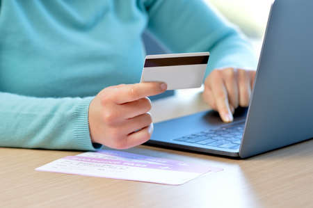 Cropped shot of a woman hands paying boarding pass with credit card at home Reklamní fotografie