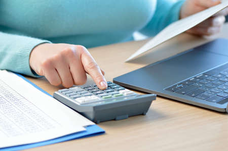 Accountant calculating with a calculator on a desk at office