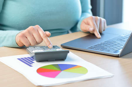 Businesswoman accounting with calculator and laptop at office
