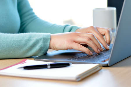 Cropped shot of a lady hands typing in a laptop on a desk at office