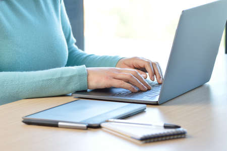 Cropped shot of a woman hands typing on a laptop keyboard on a desk at office