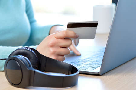 Woman hands paying music with credit card at home