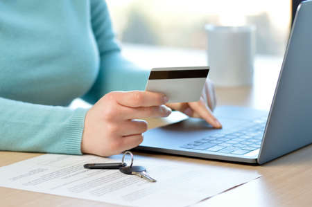 Cropped shot of a a woman hiring a home insurance on the internet with credit card at home