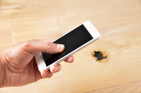 Cropped shot of an unrecognizable young man with phone to call a carpenter