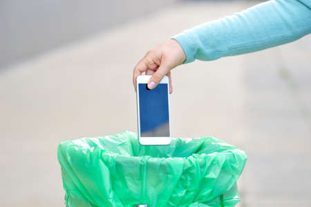 Cropped shot of a hand throwing a phone in the trash with broken screen