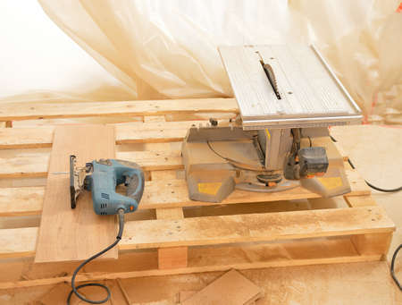 Cropped shot of a wood cutting machine in a workshop and another manual saw