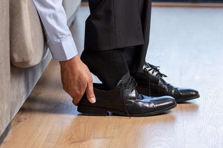 Businessman taking off shoes after work at home Banco de Imagens