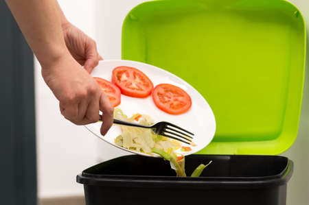 Close-up of a person throwing a half-finished banana with vegetables into the bin.Concept of food waste that is in good condition