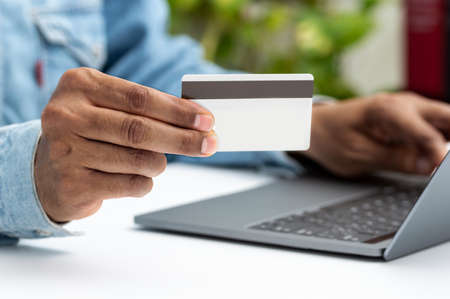 Close up of a man hands buying online with a credit card and a laptop in Ecommerce concept