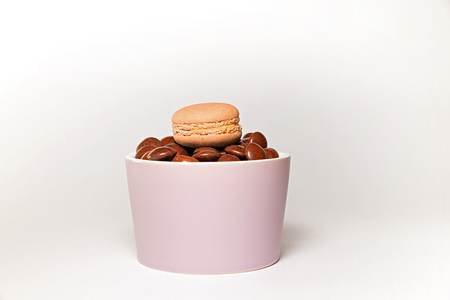 dragees: bowl of chocolate dragees with macarons