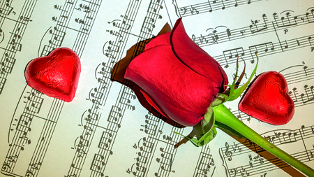 scores: Red rose on musical scores with chocolate hearts around Stock Photo