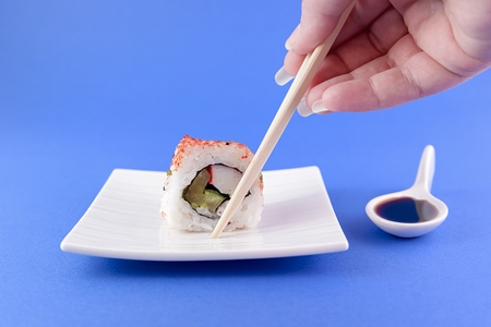 are taken: sushi taken from a hand with chopsticks Stock Photo