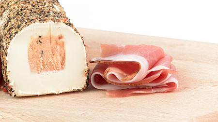 speck: speck and pepper cheese on cutting board Stock Photo