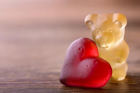 oso: osito de goma con el corazón rojo en la madera para San Valentín