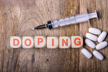 sports medicine: doping written with syringe and pills on wood Stock Photo
