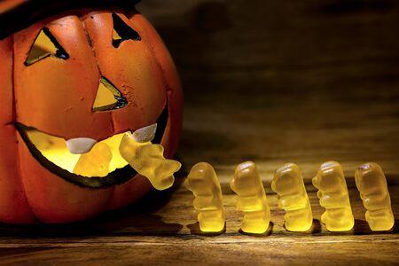gummy bear: halloween pumpkin eating a row of gummy bear for trick or treat concept