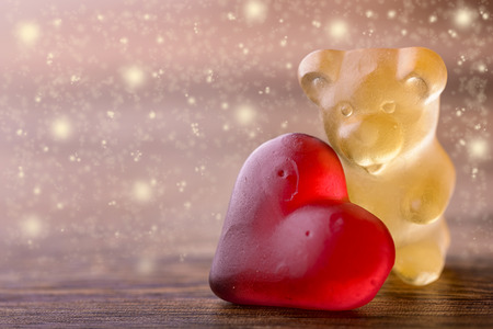gummy bear: gummy bear with red heart and glitter on wood for valentines Stock Photo