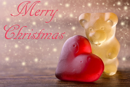 gummy bear: gummy bear with red heart and glitter on wood and merry christmas written
