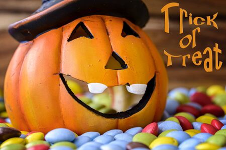 trick or treat: halloween pumpkin with chocolate candy and trick or treat written Stock Photo