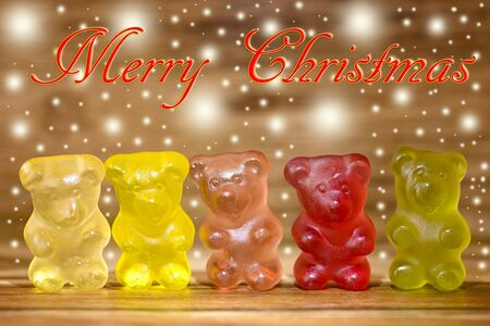 gummy bear: multicolored gummy bear and glitter on wood and merry christmas written