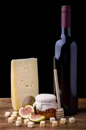 wooden stick: cheese, squares of parmesan, fig, jar of honey and bottle of red wine on wooden table