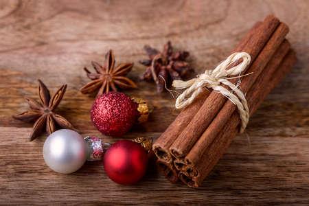 pelota: canela y an�s estrellado con bolas rojas y blancas de la Navidad en la madera Foto de archivo
