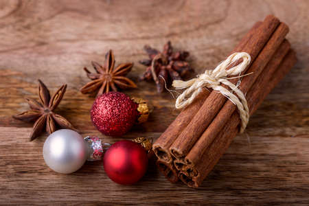 holiday celebration: cinnamon and star anise with red and white christmas balls on wood Stock Photo
