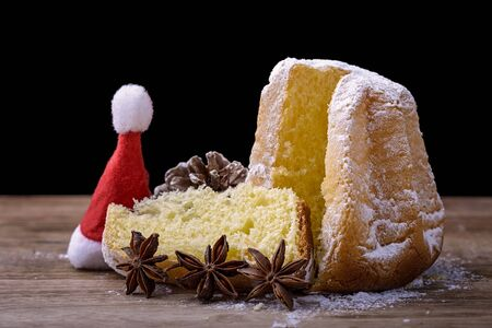cone cake cone: pandoro cake on wood with star anise, pine cone and hat of Santa Claus